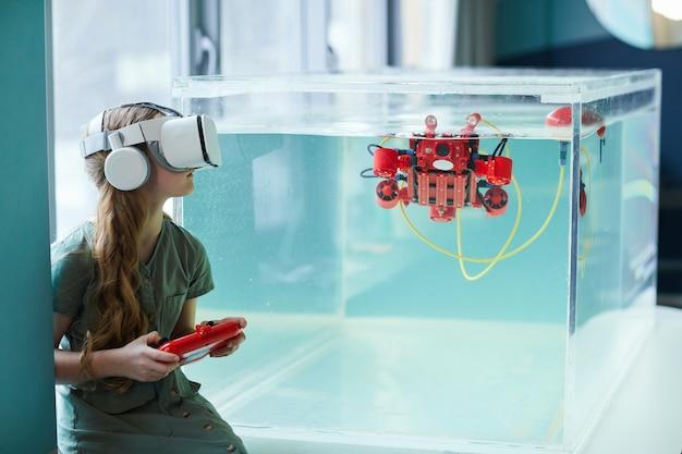 Ritratto in vista laterale di una ragazza che indossa l'auricolare vr durante l'utilizzo di una barca robotica nel laboratorio della scuola, spazio di copia