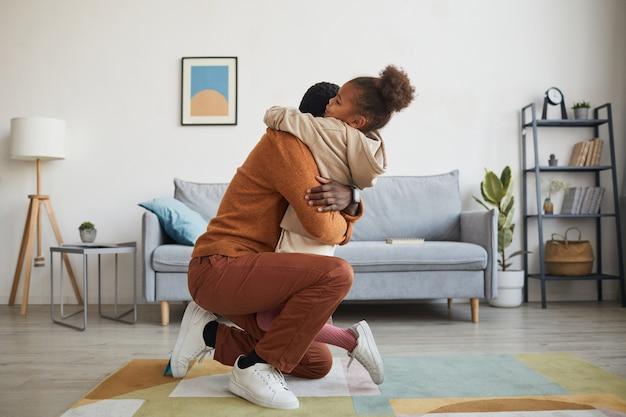 Ritratto di vista laterale del padre felice che abbraccia la bambina dopo essere tornato a casa dal lavoro il giorno del papà, copia spazio