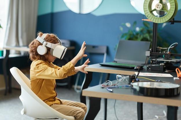 Ritratto in vista laterale di un ragazzino che indossa l'auricolare vr e si allunga mentre testa la tecnologia aumentata nel laboratorio della scuola, copia spazio