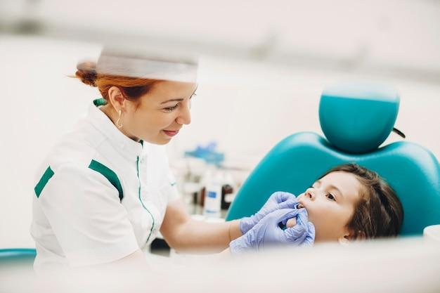Ritratto di vista laterale di un ragazzino adorabile che ha un intervento chirurgico ai denti in una stomatologia pediatrica. giovane dentista pediatrico facendo un esame dei denti.