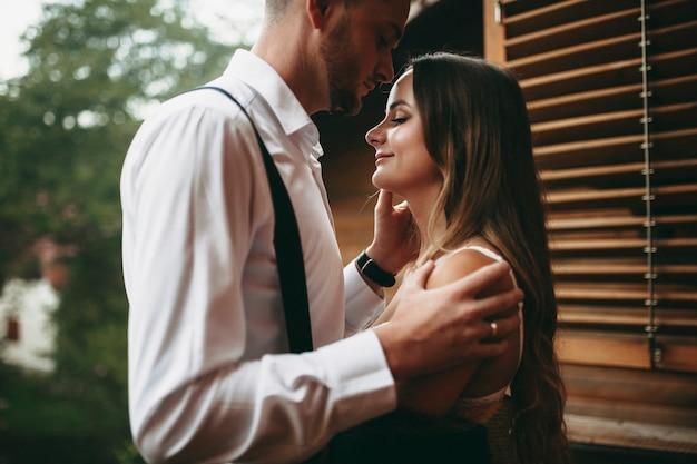 Ritratto di vista laterale di una giovane sposa adorabile che è abbracciata dal suo sposo mentre lo sposo sta baciando la sua fronte.