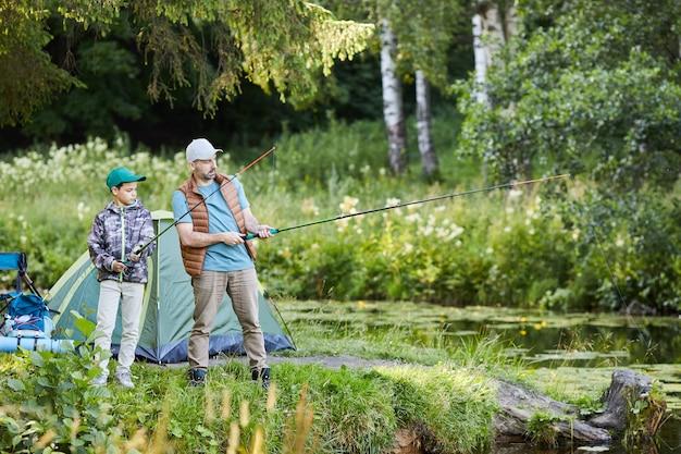 Ritratto di vista laterale del padre amorevole che insegna al figlio di pesca mentre vi godete il viaggio in campeggio insieme, copia dello spazio