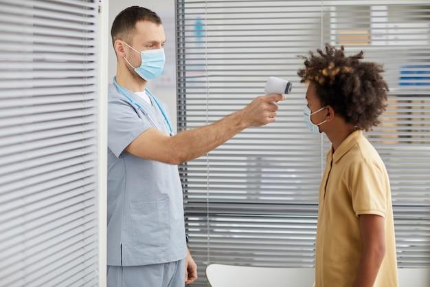 Ritratto di vista laterale del medico maschio che controlla la temperatura del ragazzo afro-americano che indossa la maschera mentre aspetta in fila presso la clinica medica, copia spazio