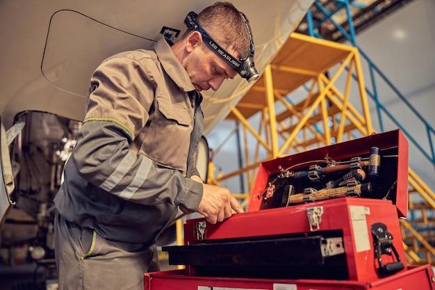 Ritratto di vista laterale dell'ingegnere aeronautico dell'uomo nell'hangar che sceglie gli strumenti per la riparazione e la manutenzione dell'aereo a reazione del passeggero