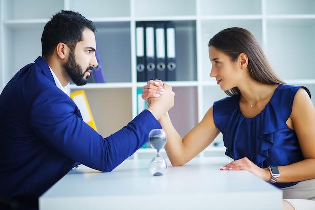 Ritratto di vista laterale dell'uomo e della donna armwrestling, esercitando pressione l'uno sull'altro, guardando gli occhi negli occhi, lottando per la leadership. affari, foto di concetto di società.