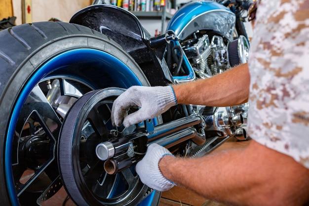 Ritratto di vista laterale dell'uomo che lavora nel garage che ripara motociclo