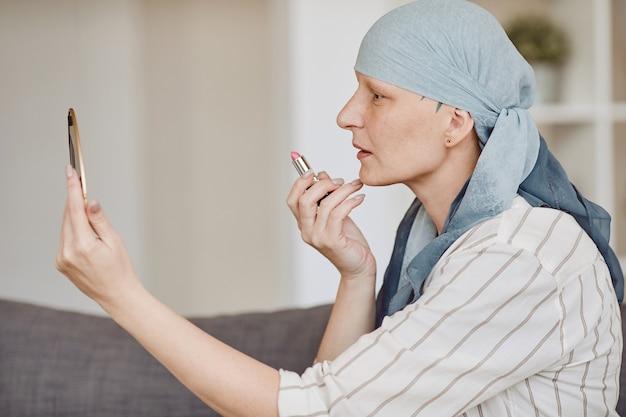Ritratto di vista laterale della donna calva matura che si mette il trucco e il rossetto mentre guarda nello specchio a casa, abbracciando la bellezza, l'alopecia e la consapevolezza del cancro