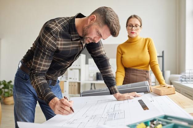 Ritratto di vista laterale dell'architetto barbuto maturo che disegna le cianografie mentre levandosi in piedi dalla scrivania in ufficio con il collega femminile nella priorità bassa