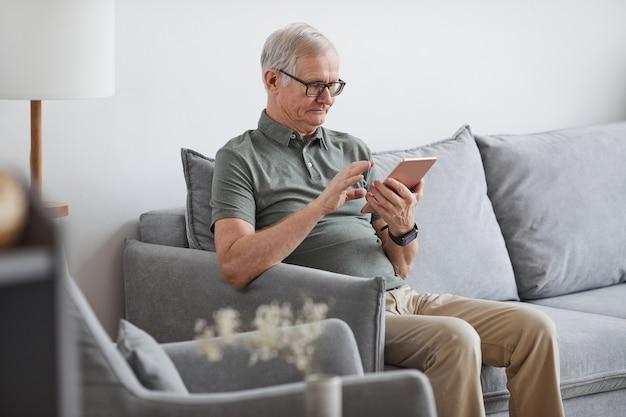 Ritratto di vista laterale di un uomo anziano moderno che utilizza un tablet digitale a casa mentre è seduto sul divano in interni minimi, spazio di copia