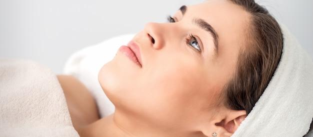 Ritratto di vista laterale della giovane donna pensierosa che si trova sulla tabella dell'estetista mentre attende la procedura cosmetica nel salone di bellezza