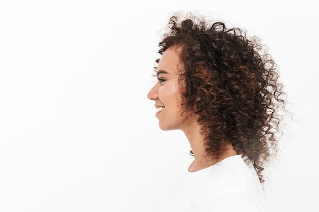 Ritratto di vista laterale di una ragazza africana piuttosto casual in piedi isolata su un muro bianco
