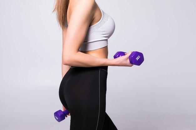 Ritratto di vista laterale di una bella giovane sportiva facendo esercizi con manubri isolati su un muro bianco