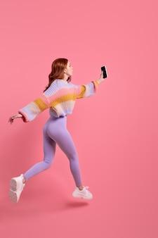 Ritratto di vista laterale di una donna dai capelli rossi in leggins che corre saltando in avanti con lo smartphone in mani...