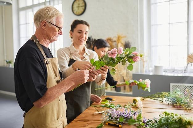 Ritratto di vista laterale dell'uomo anziano che accusa le composizioni floreali nello spazio della copia dell'officina dei fioristi