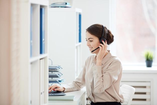 Ritratto di vista laterale della donna di affari sorridente che parla al microfono mentre lavora con il computer portatile nell'interiore dell'ufficio
