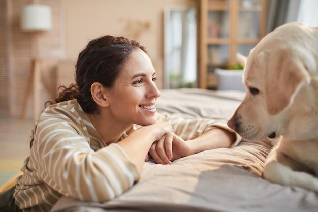 Ritratto di vista laterale di una giovane donna sorridente che guarda il cane con amore e cura in un accogliente interno di casa, copia spazio