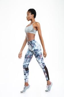 Ritratto di vista laterale di una donna afroamericana sportiva in piedi isolata su uno sfondo bianco