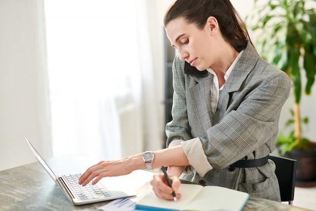 Ritratto di vista laterale della donna di affari sollecitata che parla dal telefono e che utilizza computer portatile mentre lavorando allo scrittorio in ufficio, spazio della copia