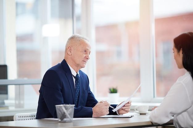 Ritratto di vista laterale dell'uomo d'affari maggiore di successo che intervista giovane donna per posizione di lavoro in ufficio