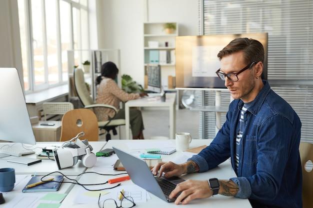 Ritratto in vista laterale di uno sviluppatore it tatuato che progetta software vr mentre si utilizza il computer e si lavora in ufficio, spazio di copia