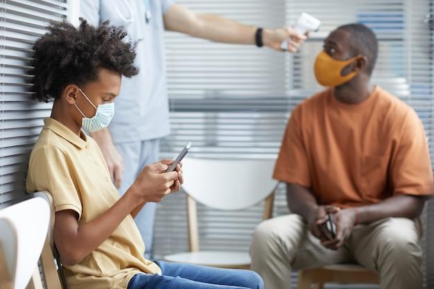 Ritratto di vista laterale del ragazzo adolescente afro-americano che utilizza lo smartphone mentre aspetta in fila in ospedale con medico maschio che controlla la temperatura in background, spazio di copia