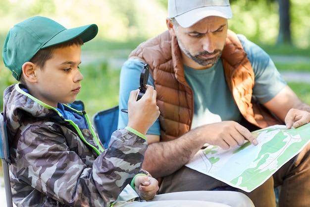 Ritratto di vista laterale del ragazzo adolescente guardando la bussola mentre vi godete il viaggio in campeggio con il padre, lo spazio della copia
