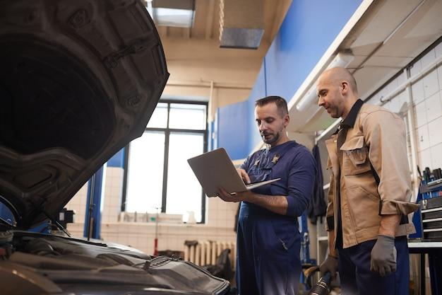 Ritratto di vista laterale di due meccanici di automobile utilizzando il computer portatile durante l'ispezione del veicolo in officina di riparazione auto, copia dello spazio