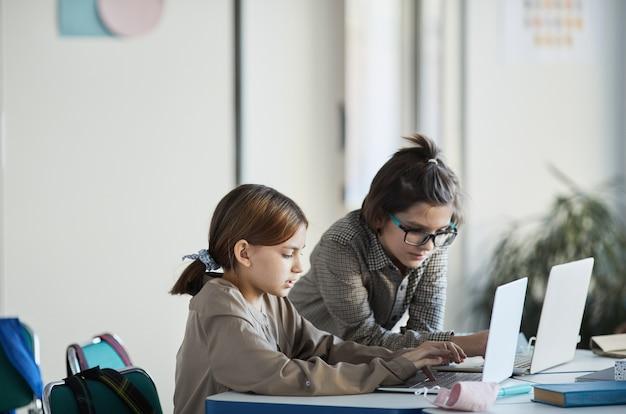 Ritratto in vista laterale di due bambini che utilizzano computer in interni minimi della scuola, spazio di copia