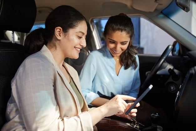 Ritratto di vista laterale di due giovani donne mediorientali che utilizzano smartphone e sorridono mentre erano seduti in macchina