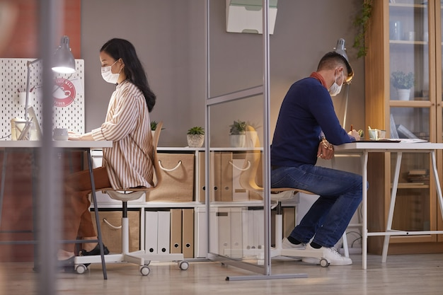 Vista laterale verticale di due persone che indossano maschere in ufficio mentre si lavora alle scrivanie in cubicoli separati post pandemia, spazio di copia