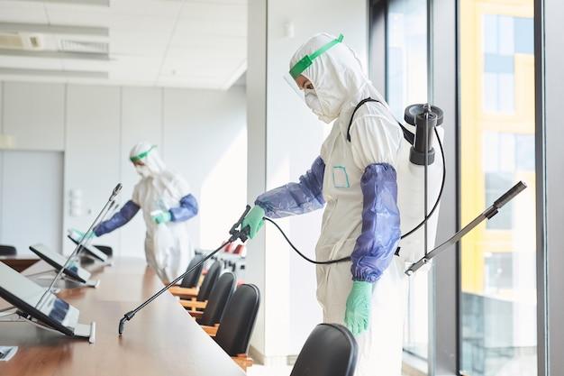 Vista laterale il ritratto di due lavoratori che indossano tute ignifughe disinfettando la sala conferenze in ufficio,