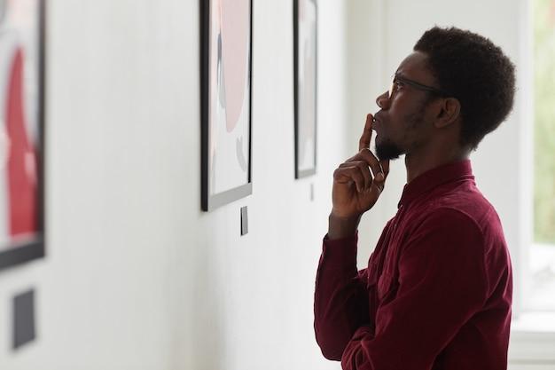 Vista laterale ritratto di giovane uomo afro-americano guardando i dipinti e pensando alla galleria d'arte o alla mostra museale,