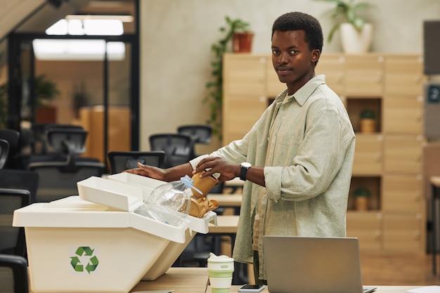 Ritratto di vista laterale di giovane uomo afro-americano che mette il bicchiere di carta nel bidone della raccolta differenziata in ufficio, copia dello spazio