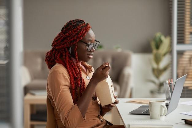 Ritratto di vista laterale di giovane donna afro-americana che mangia pranzo da asporto e guardando lo schermo del laptop mentre si gode il lavoro da ufficio a casa, copia spazio