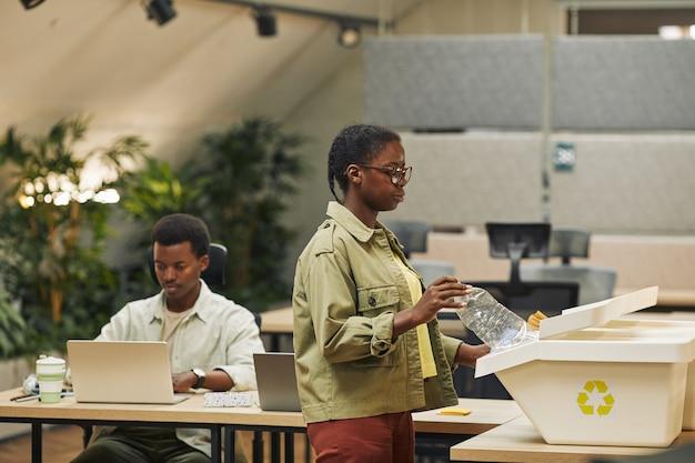 Ritratto di vista laterale di giovane donna afro-americana che mette il bicchiere di carta nel cestino per la raccolta differenziata in ufficio, copia dello spazio
