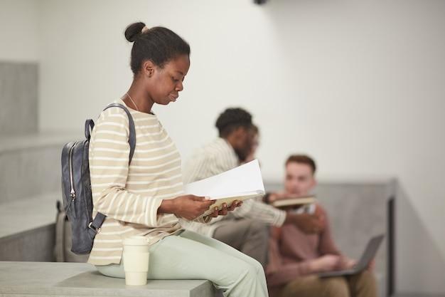 Vista laterale ritratto di giovane donna afro-americana che legge libri nella moderna lounge del college, copia spazio