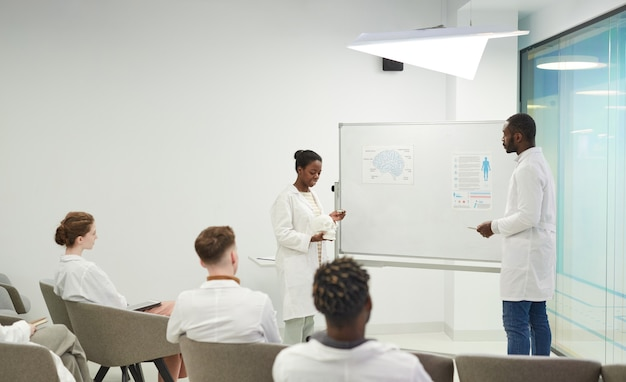 Vista laterale ritratto di giovane donna afro-americana in piedi davanti alla lavagna mentre fa una presentazione durante il seminario medico al college, copia spazio