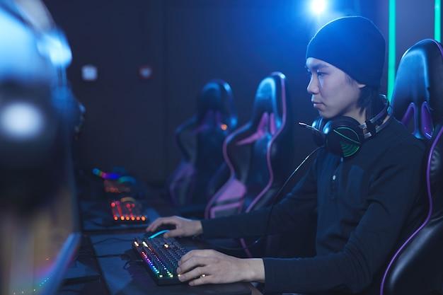 Ritratto di vista laterale di giovane uomo asiatico che gioca ai videogiochi in cyber scuro come interni, copia dello spazio