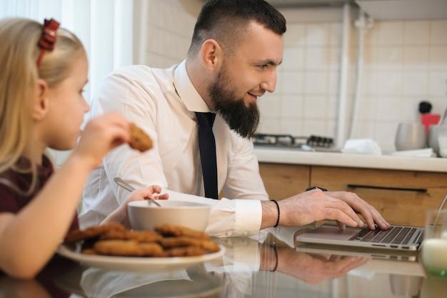Ritratto di vista laterale di un giovane padre barbuto vestito in tuta prima di andare a lavorare guardando il suo laptop in cucina mentre sua figlia sta mangiando biscotti.