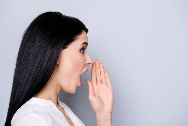 Ritratto di vista laterale di giovane donna affascinante che tiene la sua mano vicino alla bocca e che racconta notizie interessanti