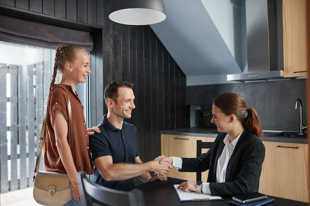 Ritratto in vista laterale di una giovane coppia che stringe la mano all'agente immobiliare mentre acquista una nuova casa, copia spazio