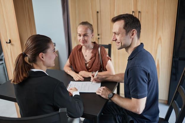 Ritratto di vista laterale di giovane coppia che firma un contratto con un agente immobiliare durante l'acquisto di una nuova casa, copia spazio