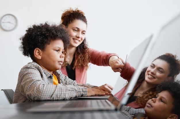 Ritratto in vista laterale di una giovane insegnante che aiuta un ragazzo afroamericano a usare il laptop durante la lezione di informatica a scuola