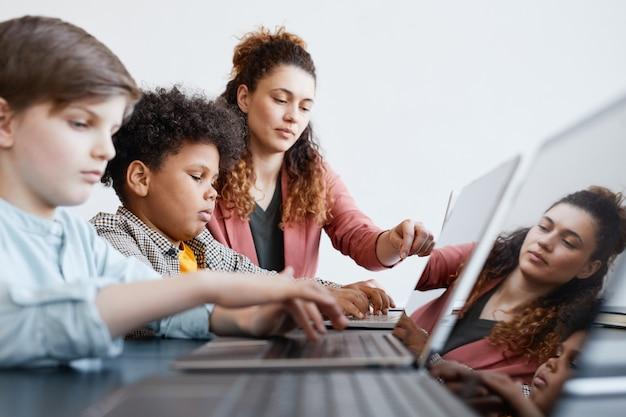 Ritratto in vista laterale di una giovane insegnante che aiuta il ragazzo a usare il laptop durante la lezione di informatica a scuola