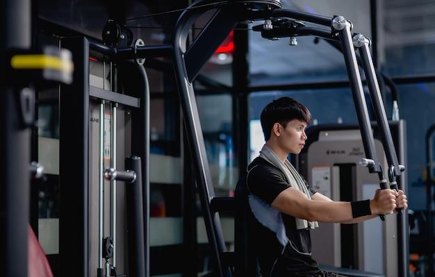 Vista laterale, ritratto giovane bell'uomo in abbigliamento sportivo seduto per fare esercizio di pressa per il torace della macchina in palestra moderna, guardando avanti,
