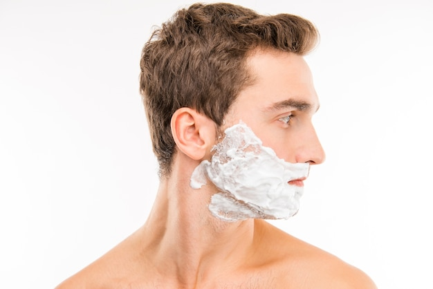 Un ritratto di vista laterale del giovane con la schiuma da barba