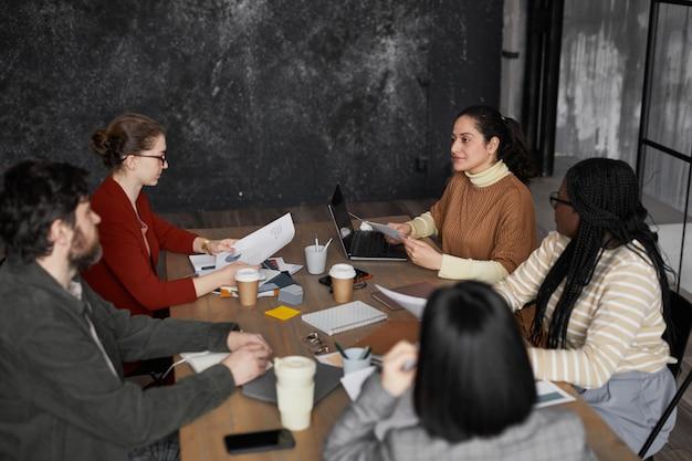 Ritratto di vista laterale di una giovane donna mediorientale che parla con un gruppo eterogeneo di colleghi