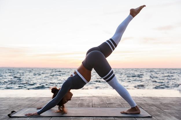 Il ritratto di vista laterale di una giovane donna che fa l'yoga si esercita