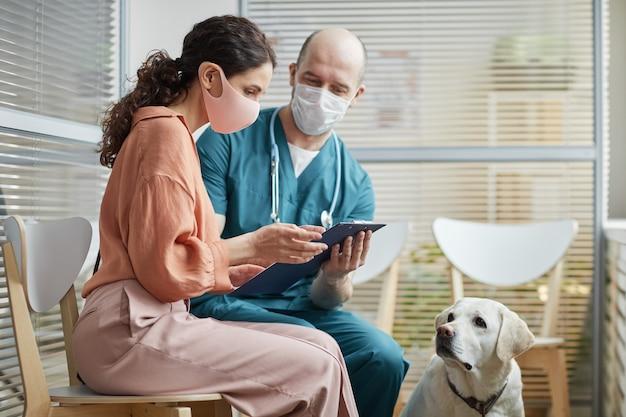 Vista laterale ritratto di giovane donna che indossa la maschera mentre parla con il veterinario nella sala d'attesa della clinica veterinaria con cane bianco, copia spazio
