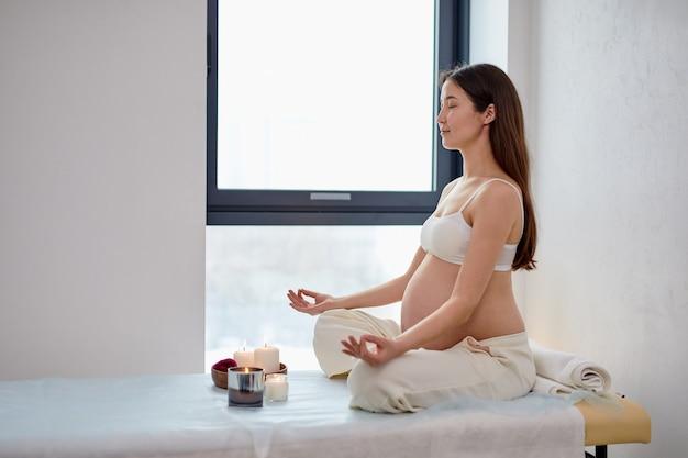 Vista laterale della donna incinta seduta in posizione yoga nella sala spa con candele, rilassante e meditando mentre indossa un abito bianco, mostrando la pancia nuda. stile di vita salute gravidanza bellezza, interni.